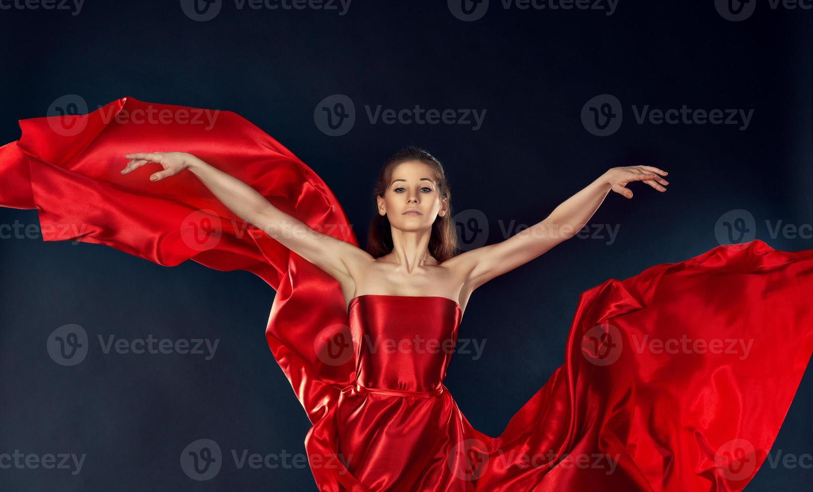 beautiful inspirational woman dancing in a red silk dress flying photo