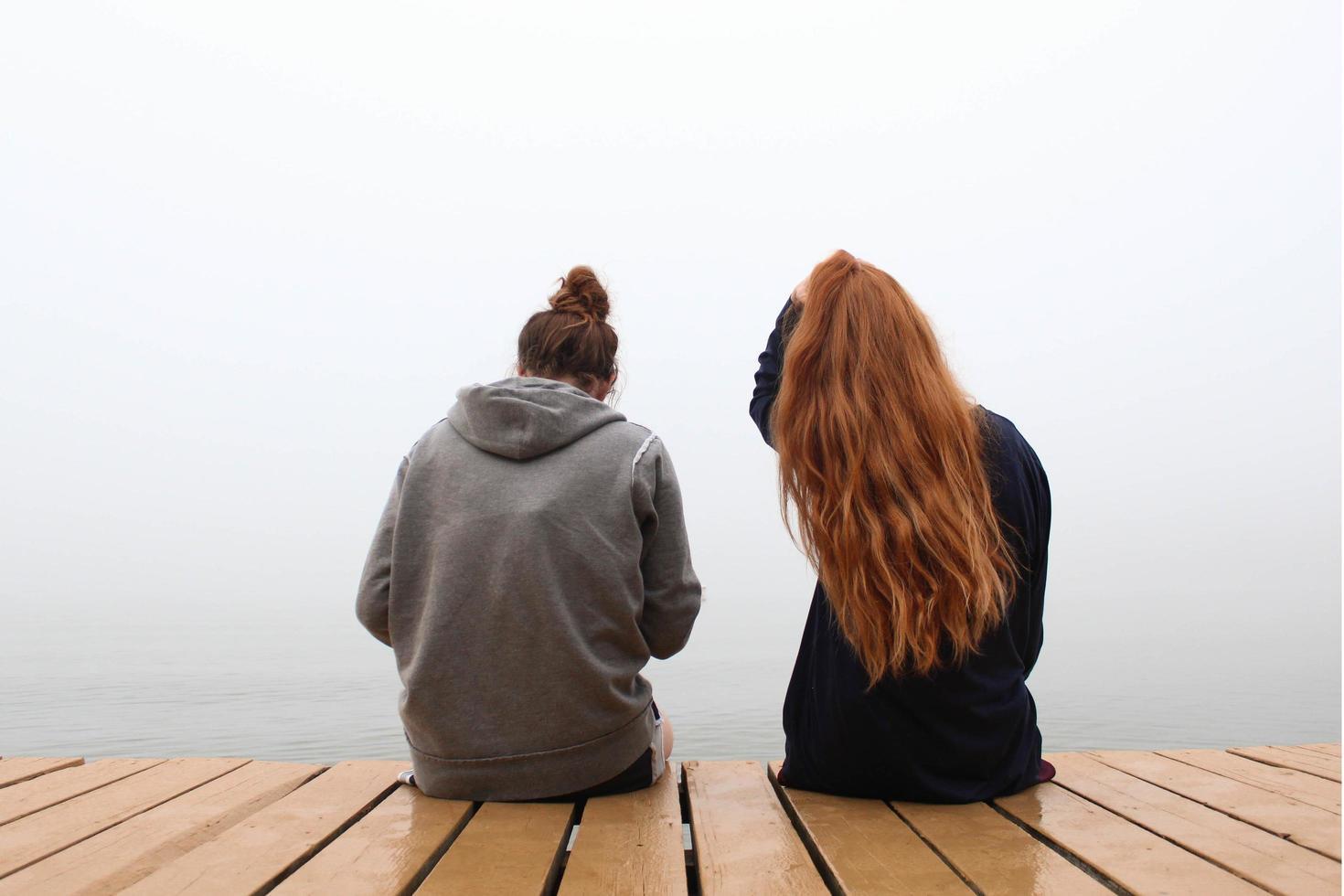 dos mujeres sentadas en un muelle de madera foto