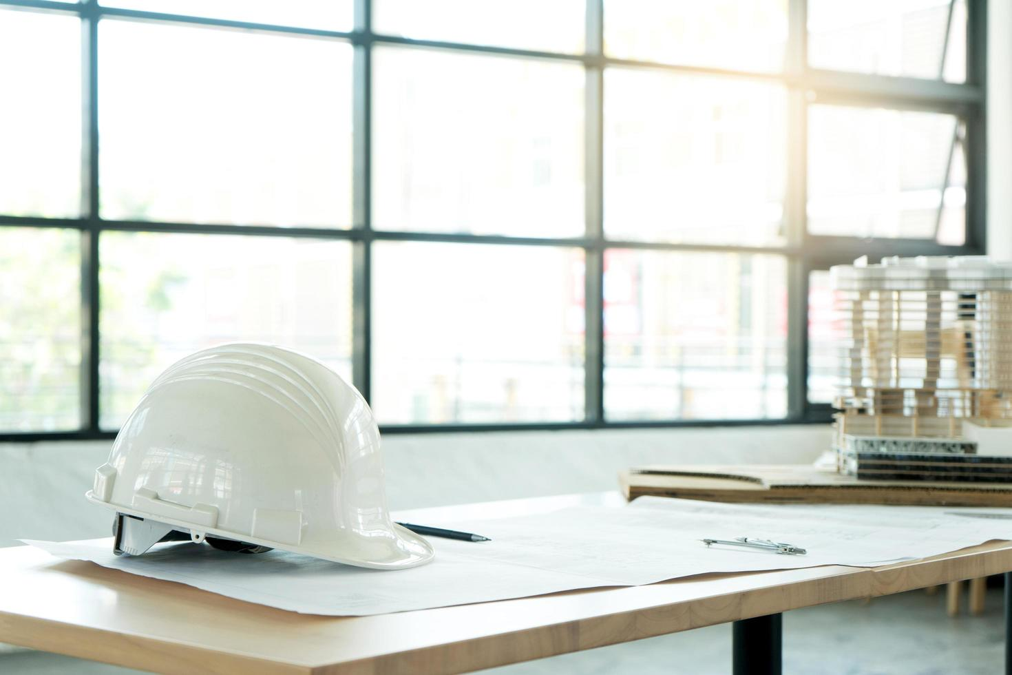 Hardhat and blueprint on table photo