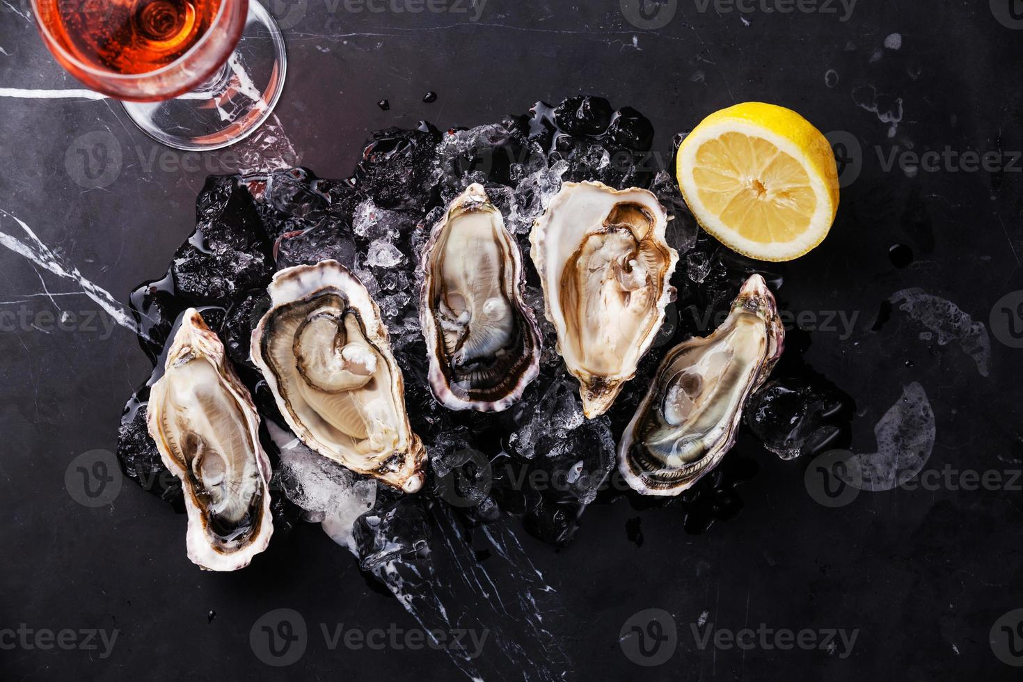 Opened Oysters with ice, lemon and wine photo