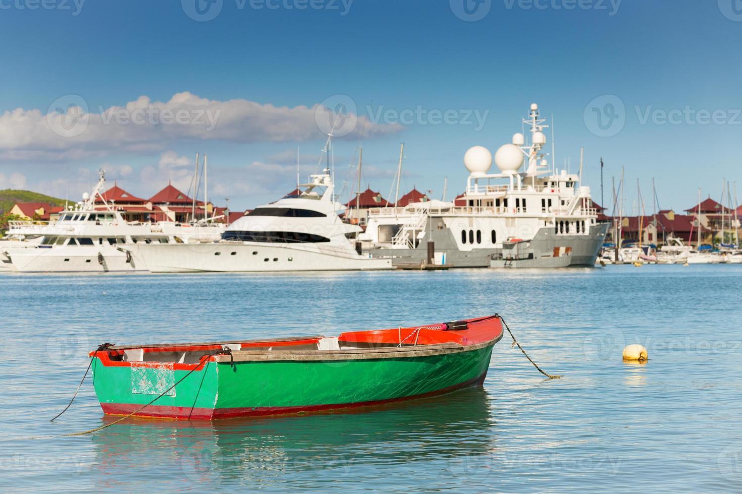 Barco de pesca con fondo de yates de lujo, isla del Edén, Mahé foto