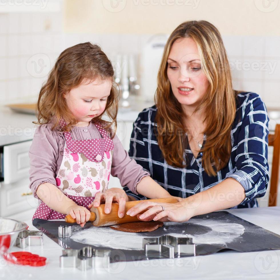 madre y niño niña horneando galletas de jengibre para cristo foto