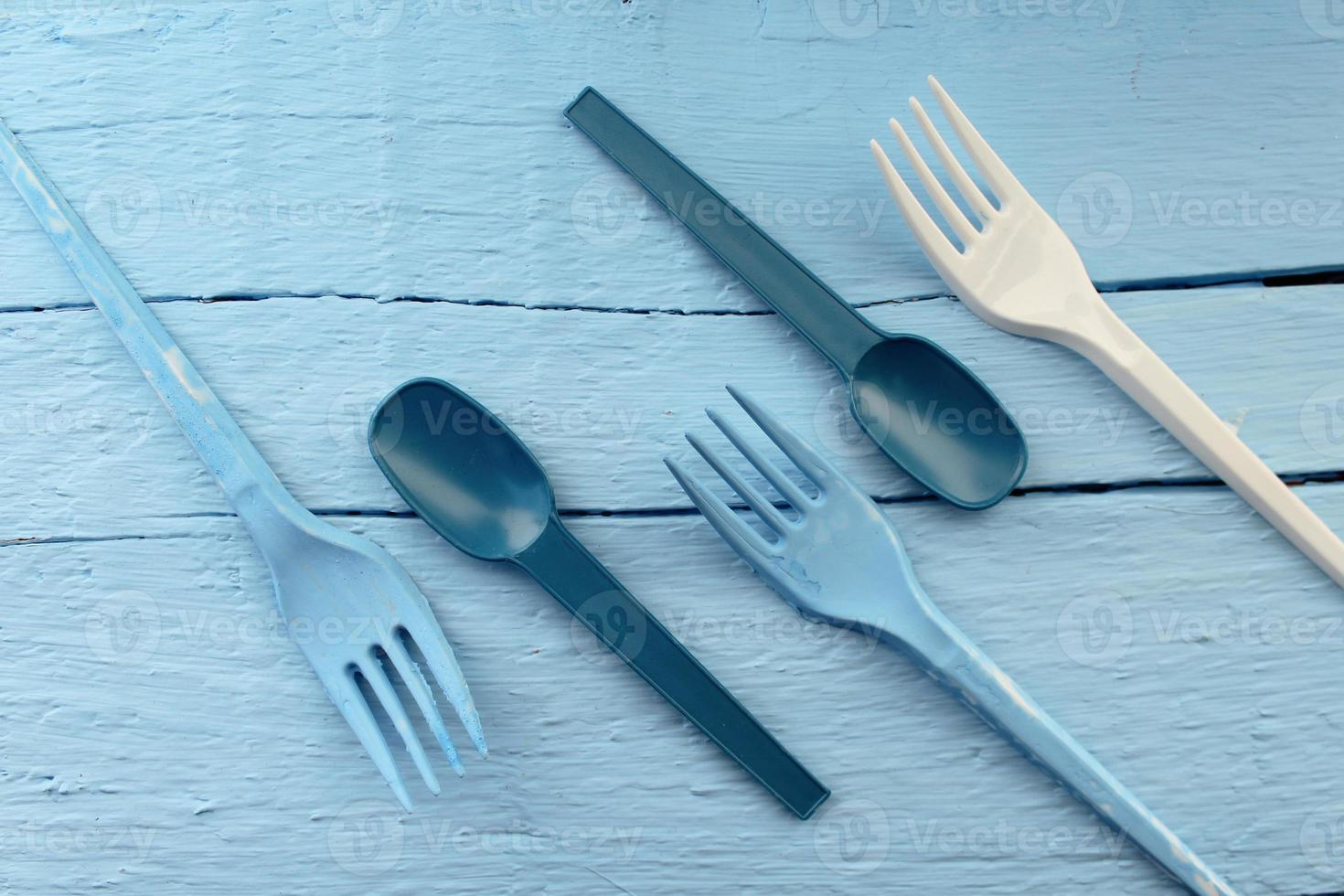 Blue and white fork and spoon on blue background photo