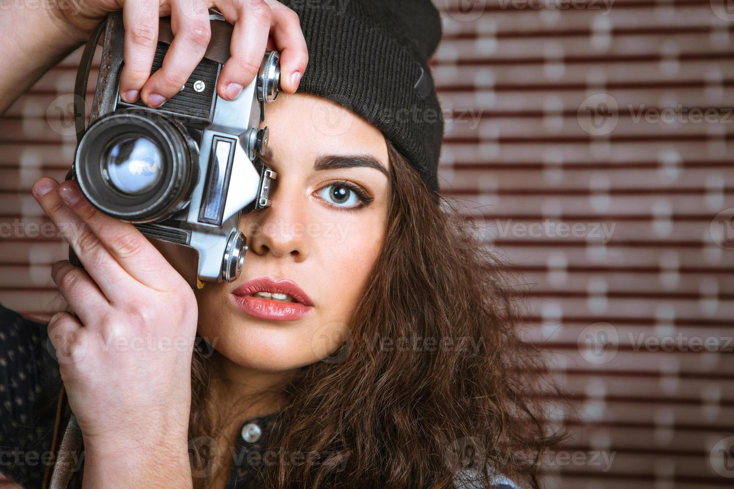 Concept for stylish young woman near brick wall photo