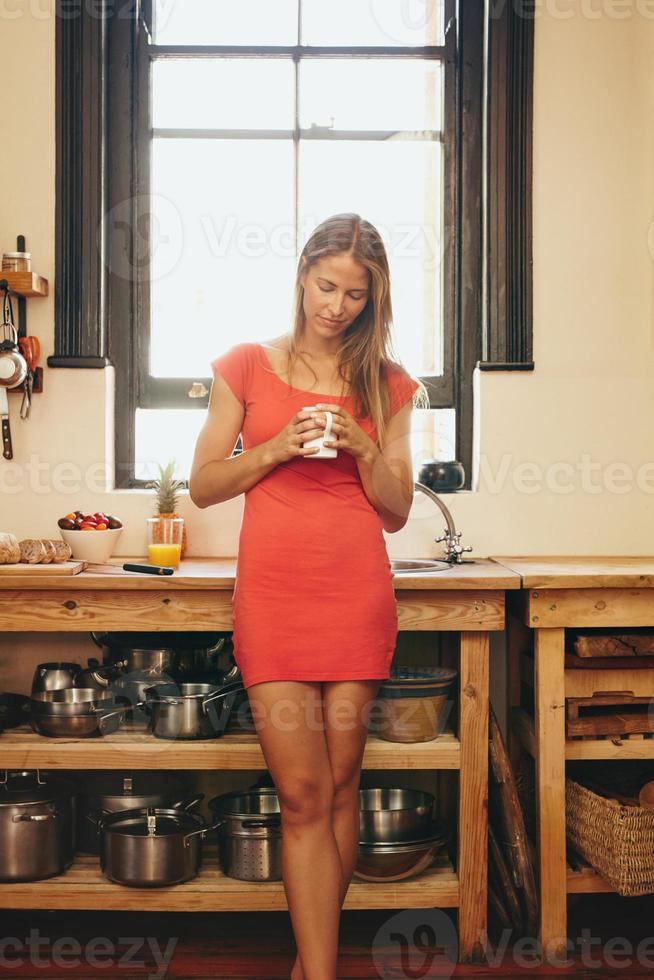 Caucasian woman with cup of coffee in her kitchen photo