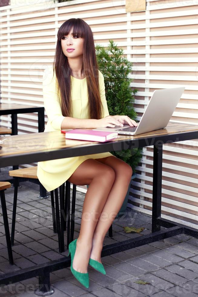 business woman working at desk typing on a laptop photo