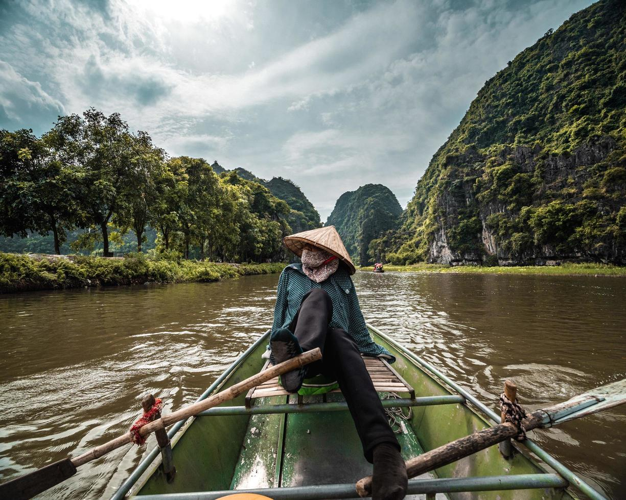 Person in conical hat in boat on river photo