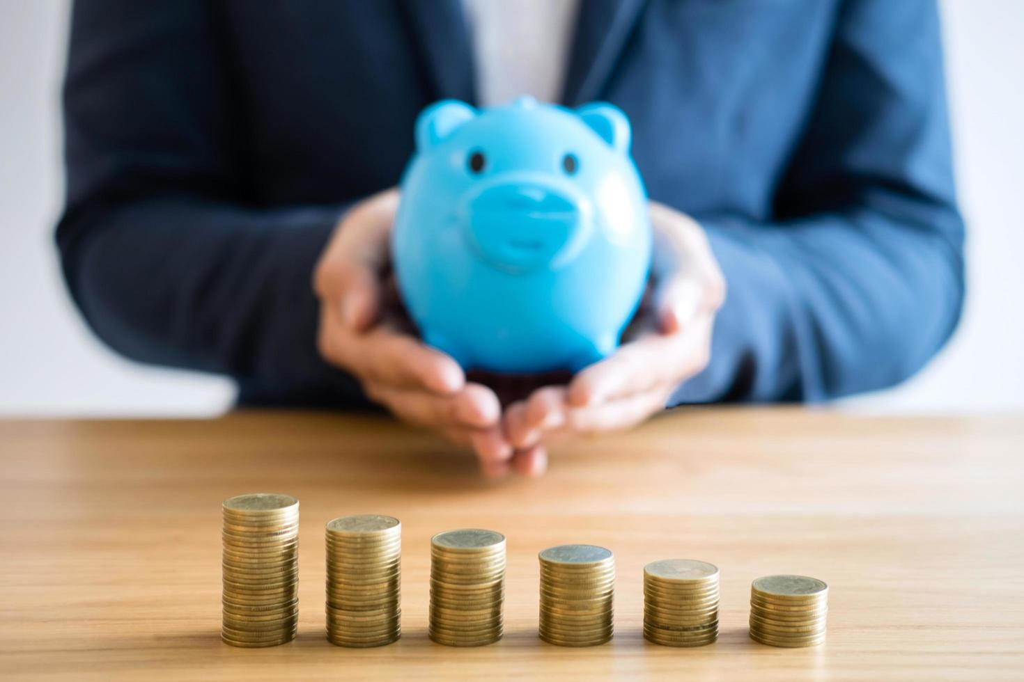Business person holding blue piggy bank  photo