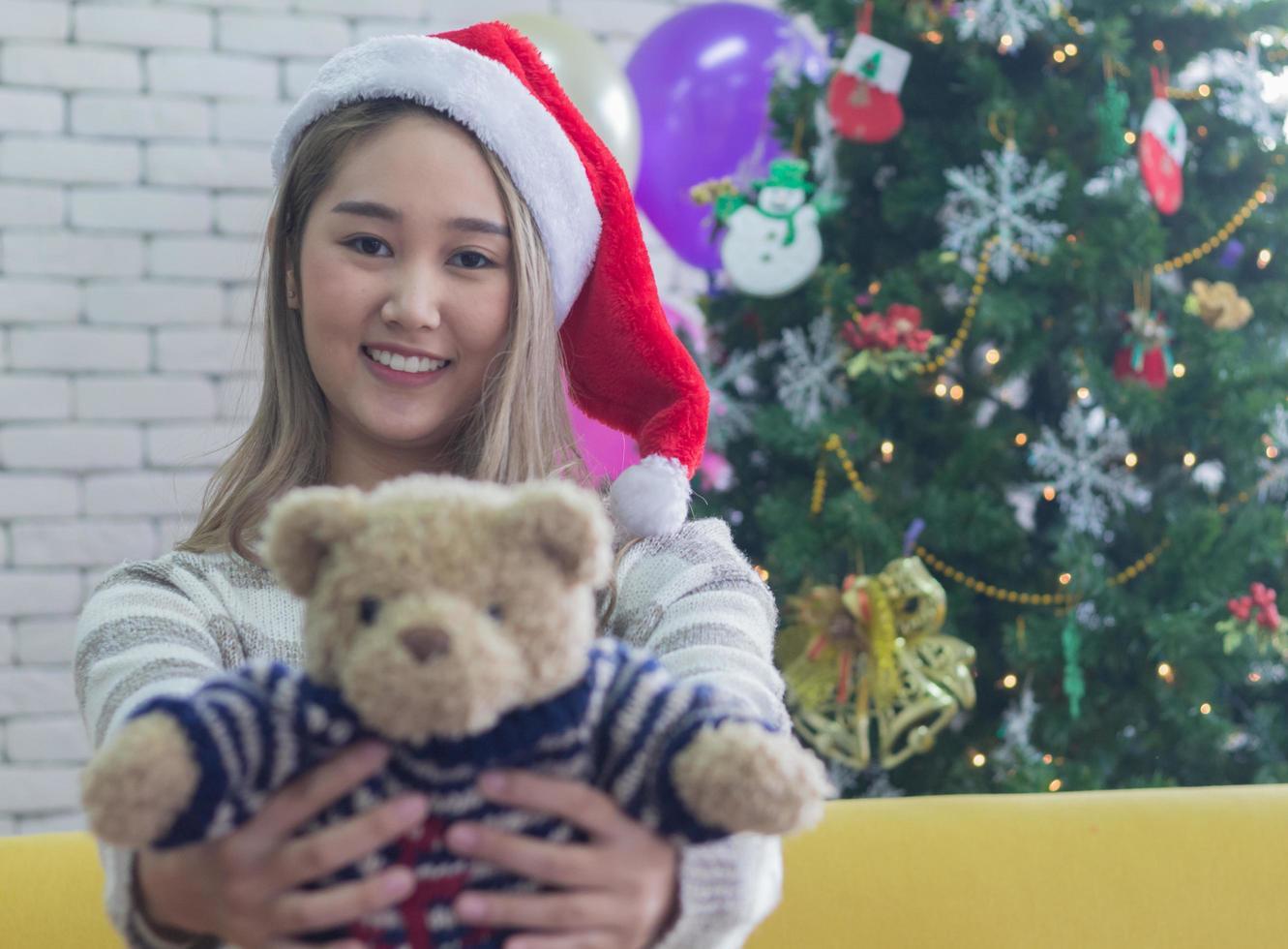 Woman holding a teddy bear wearing a Santa hat photo