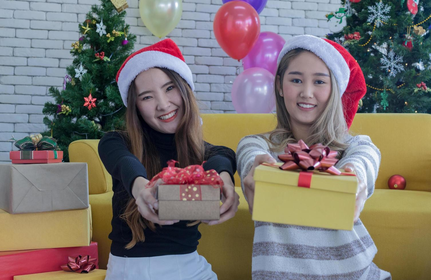 Two women holding out presents photo