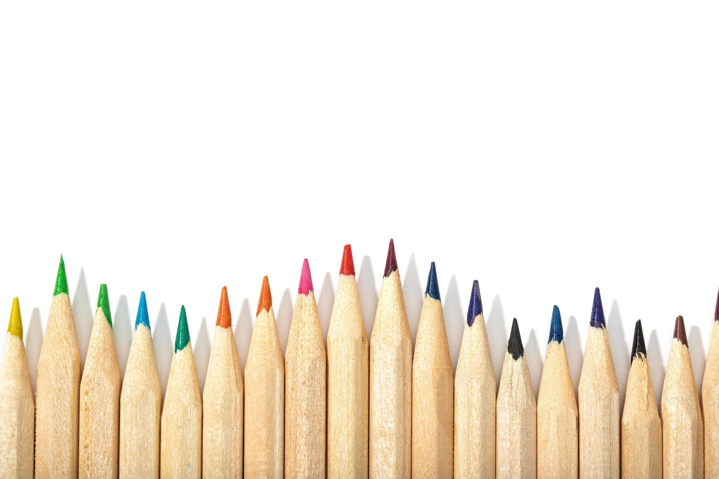 Border of colored pencils on a white background photo