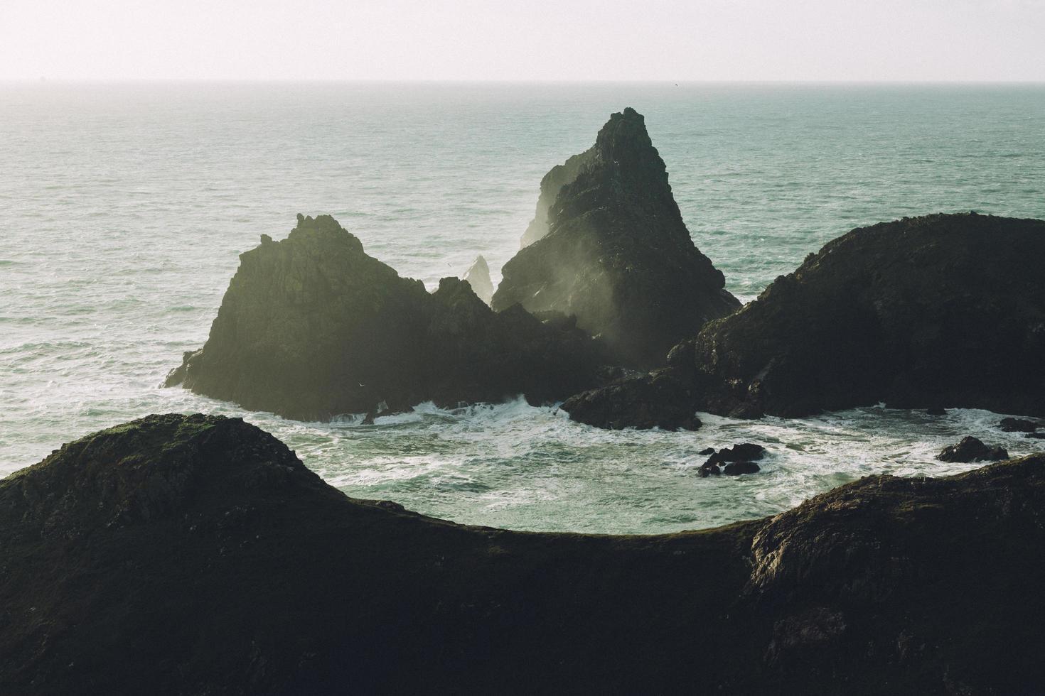 siluetas de rocas en el océano foto