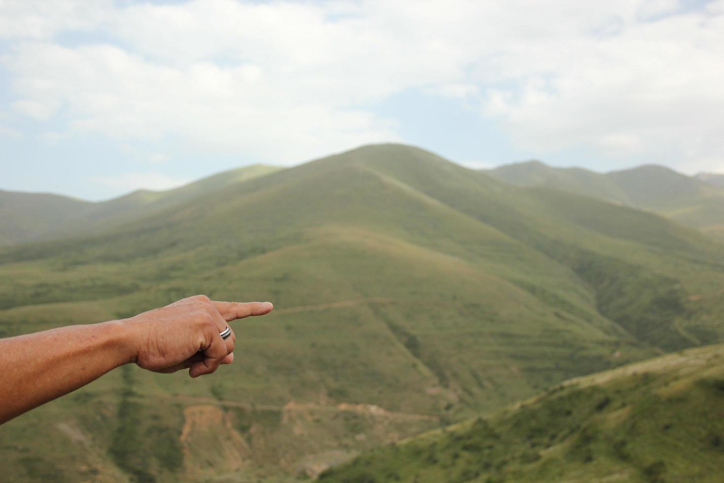 Person pointing finger toward Armenian mountains  photo