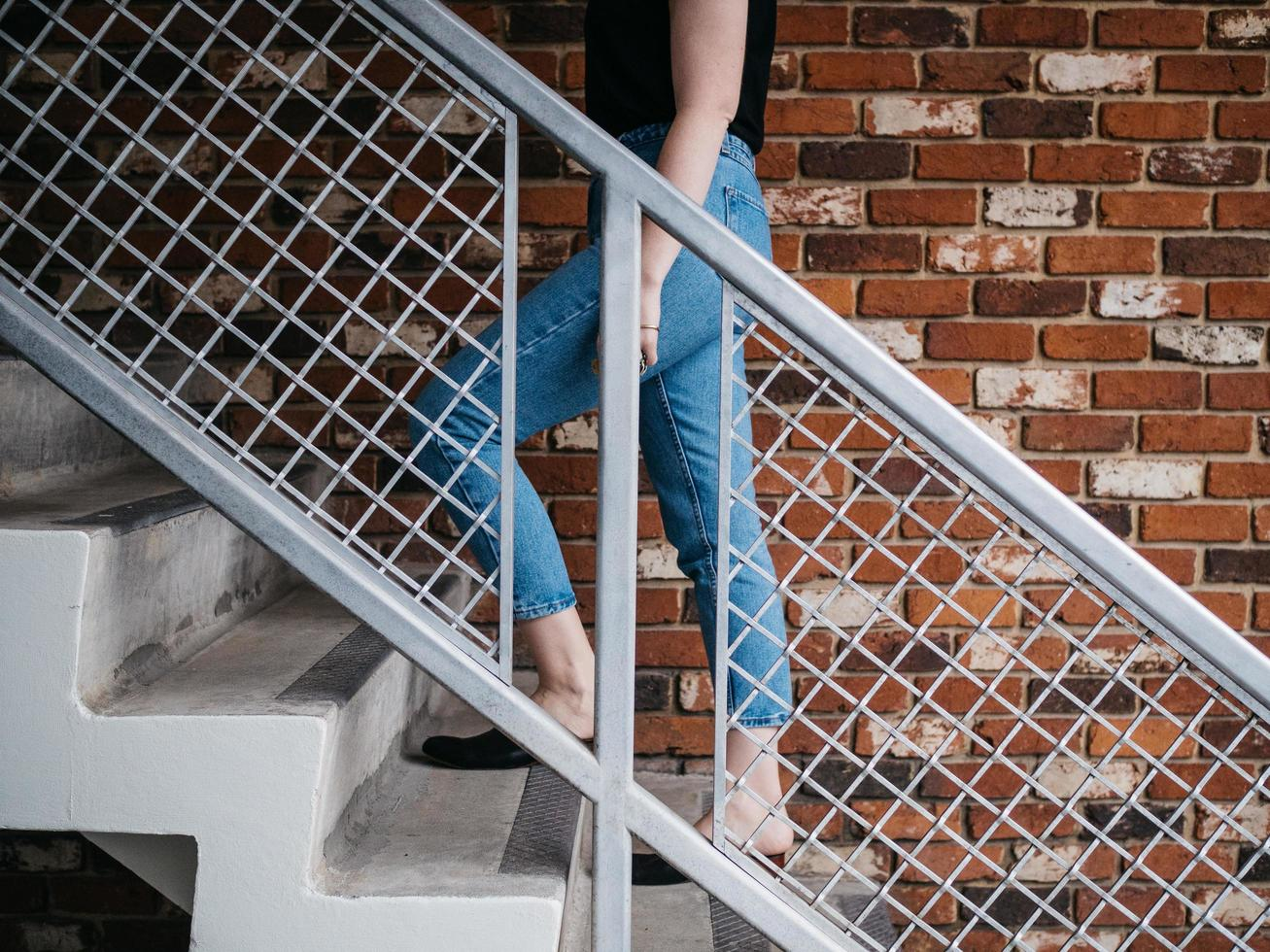 Woman walking on stairs near railling and wall photo