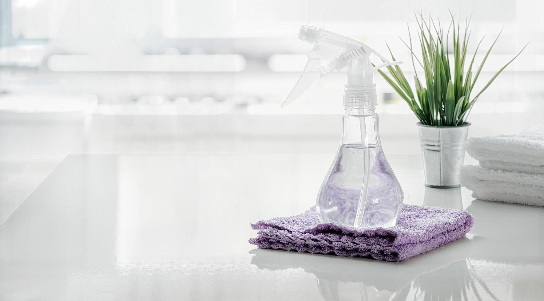 Spray bottle and towel on white table in kitchen  photo