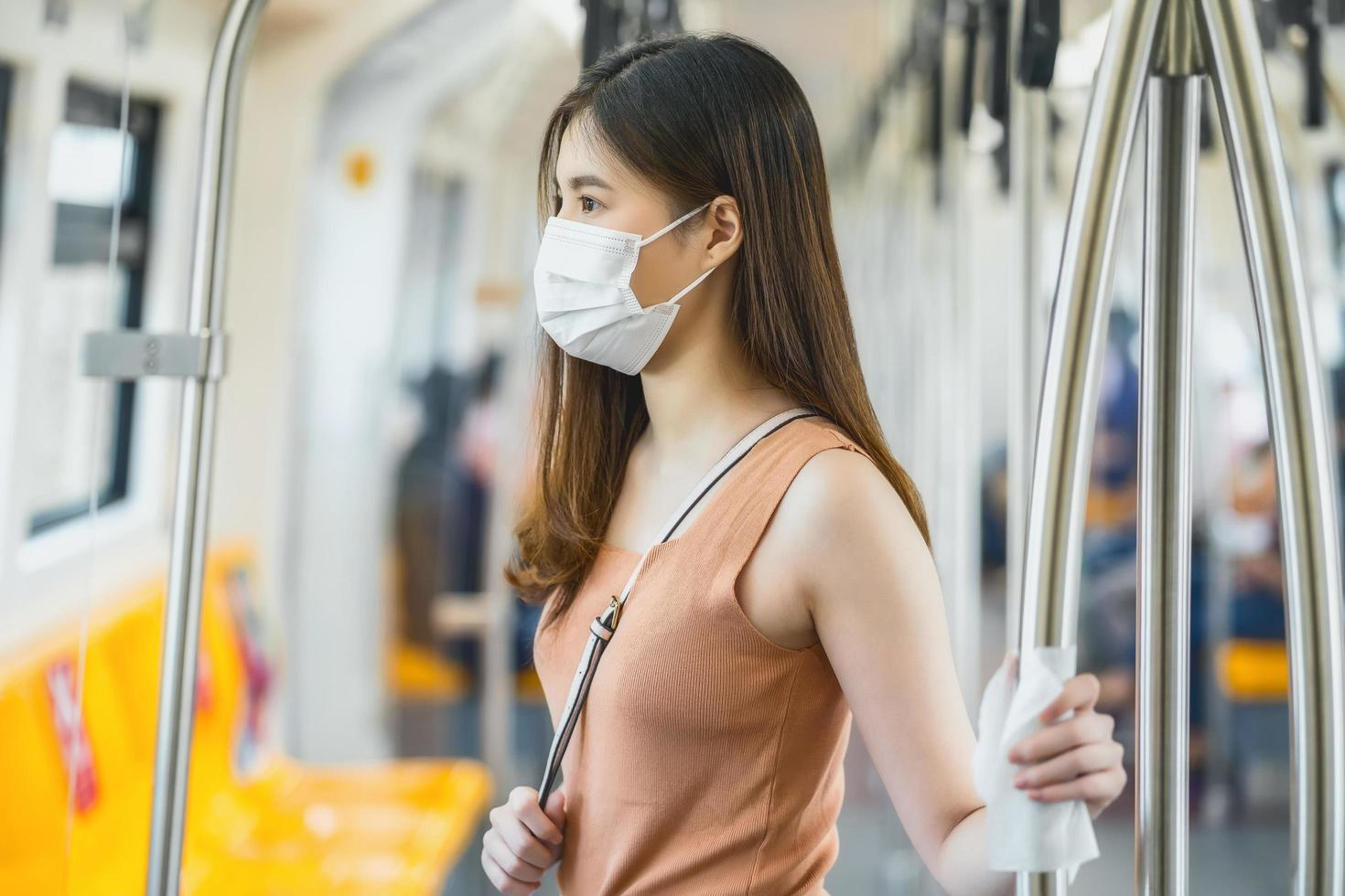 Woman riding a train with a mask on photo