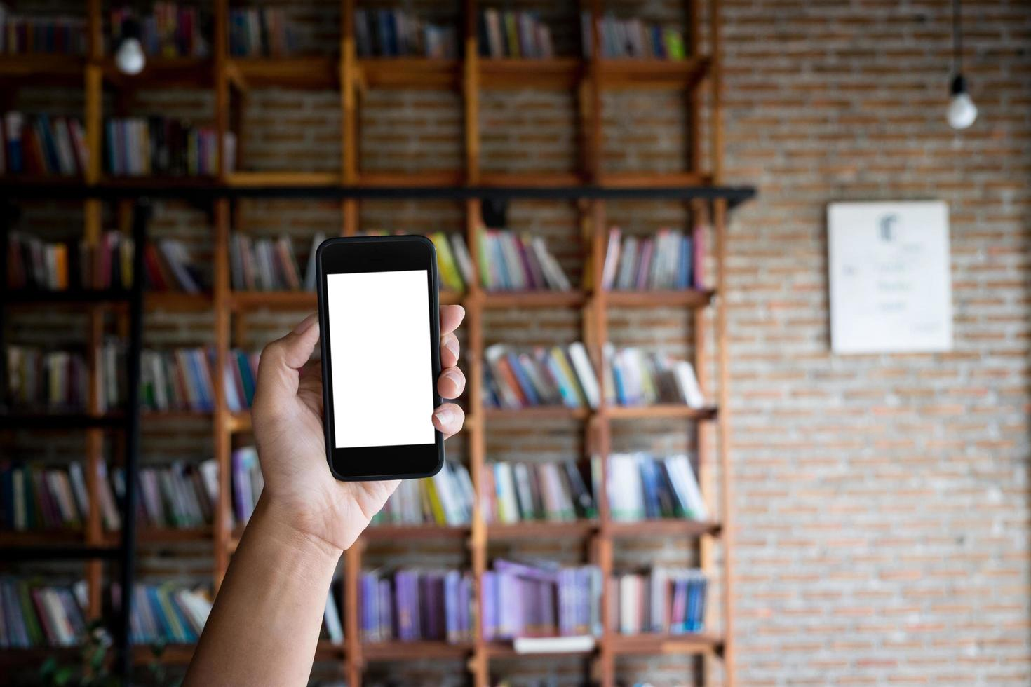 Smartphone mockup in front of a bookshelf photo