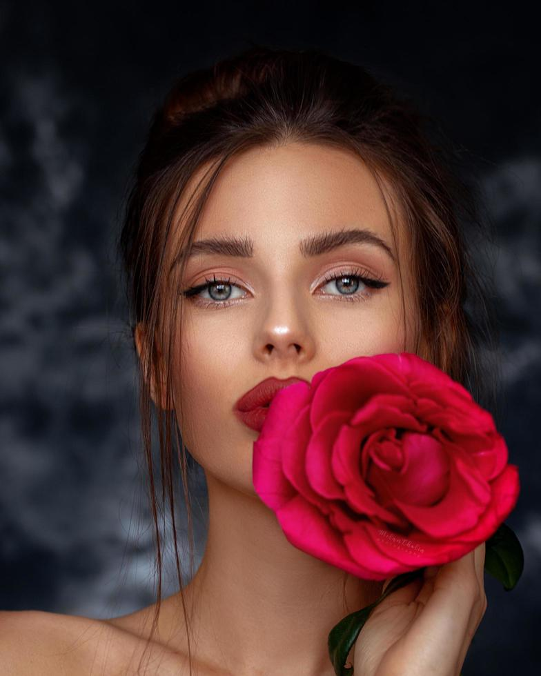 Self-confident woman with a red rose photo