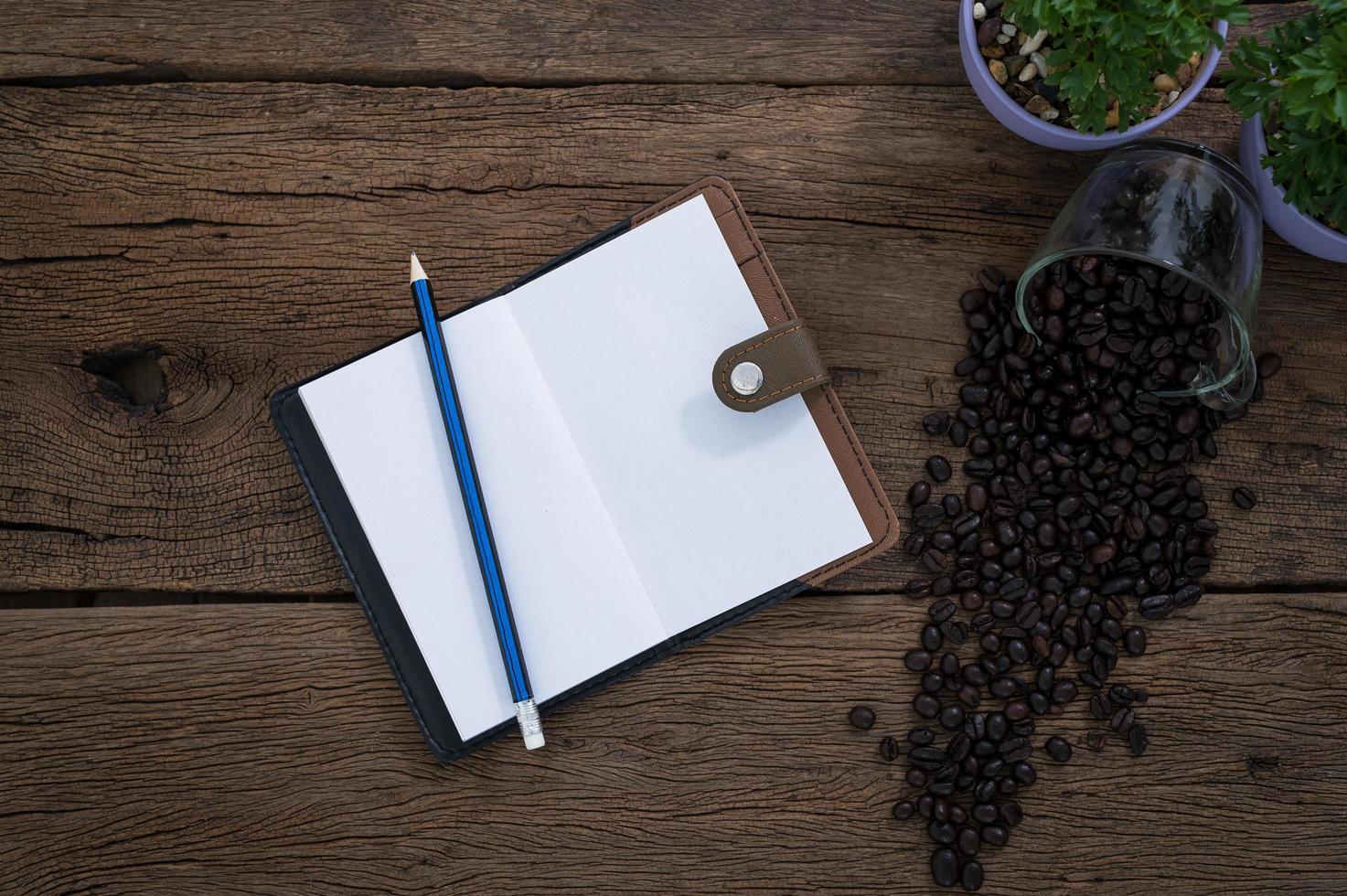 cuaderno con lápiz y granos de café foto