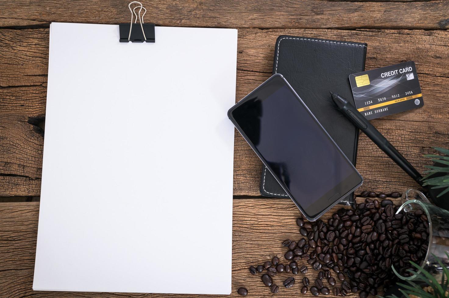 tarjeta de crédito, teléfono inteligente y papel en blanco foto