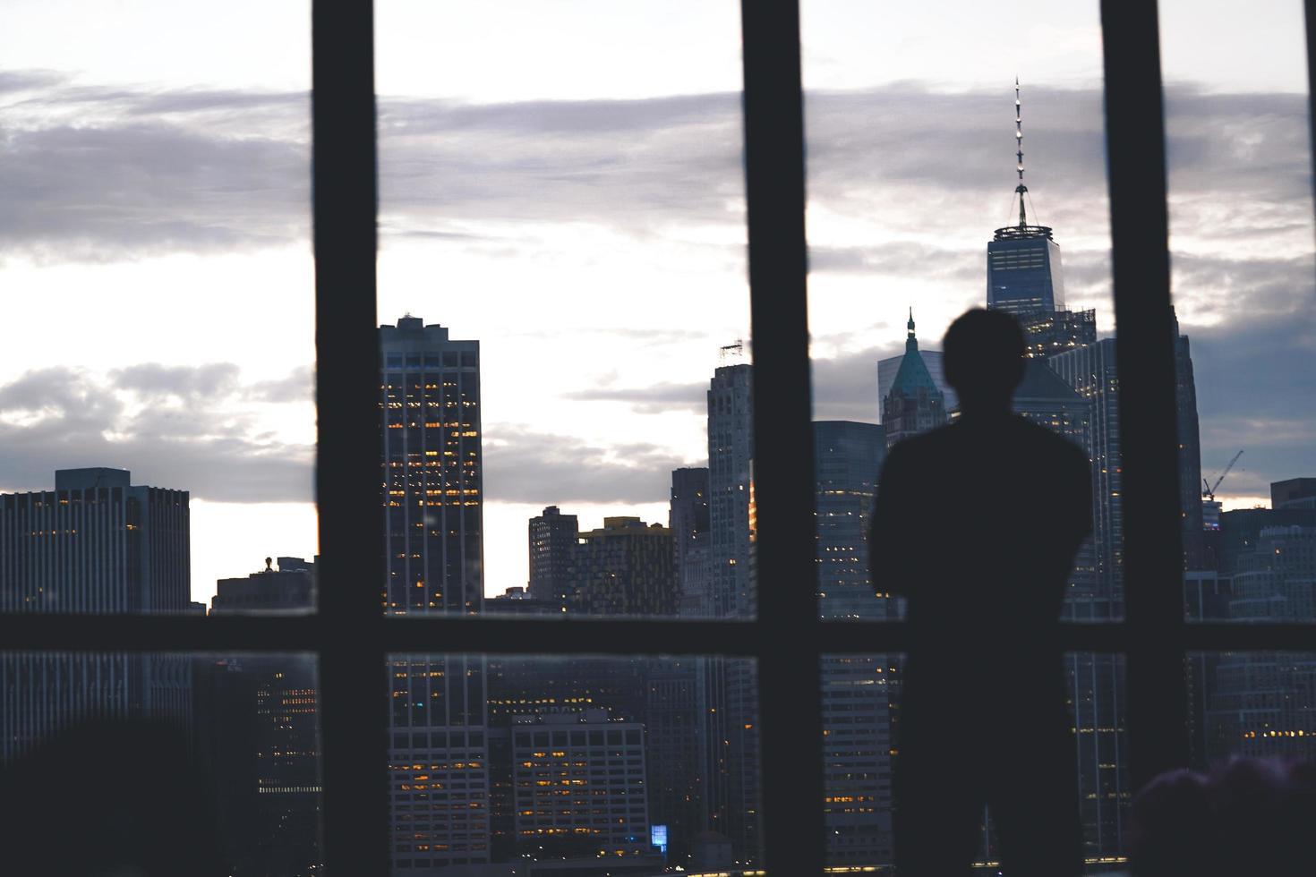 Man standing near city window photo