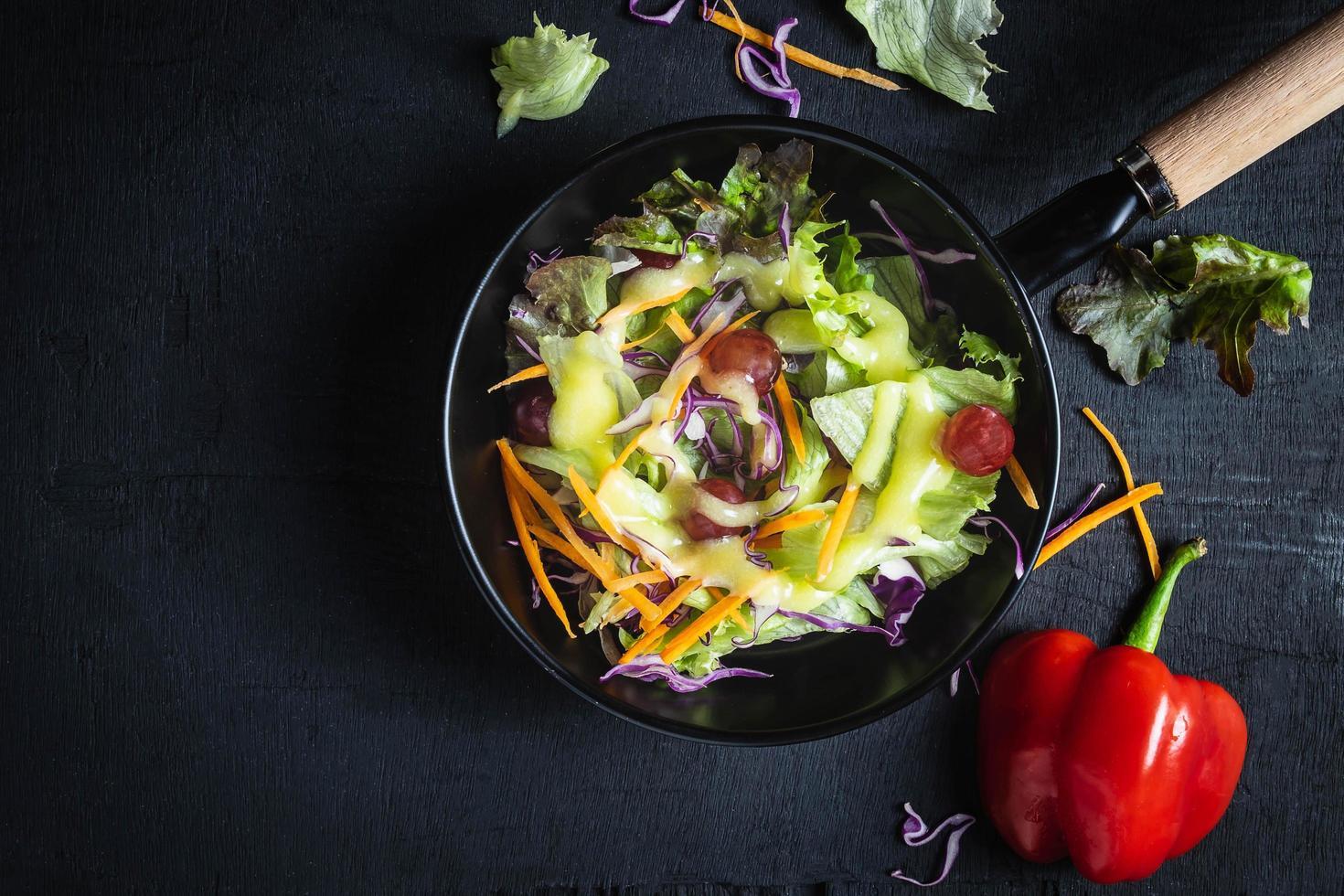 ensalada de verduras sobre fondo negro foto