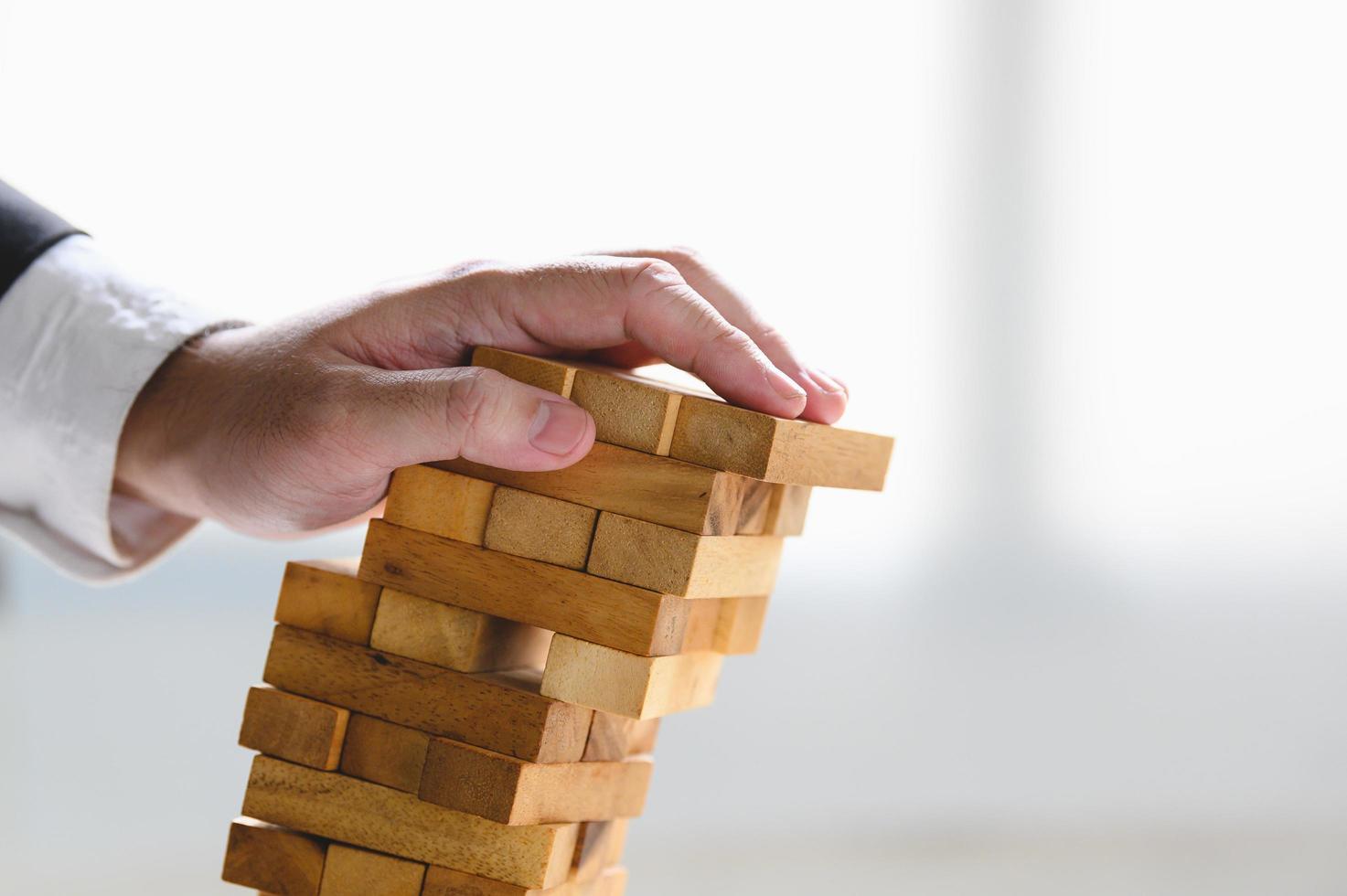 uomo d'affari che crolla torre di legno impilata foto