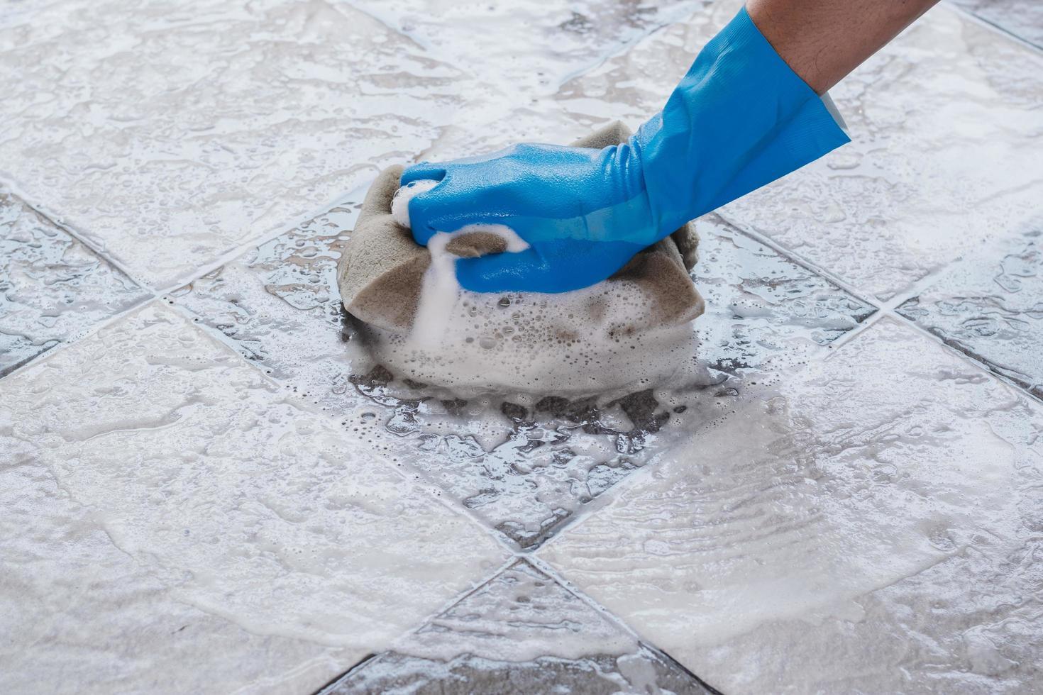 close-up van een persoon die een vloer met een spons schoonmaakt foto