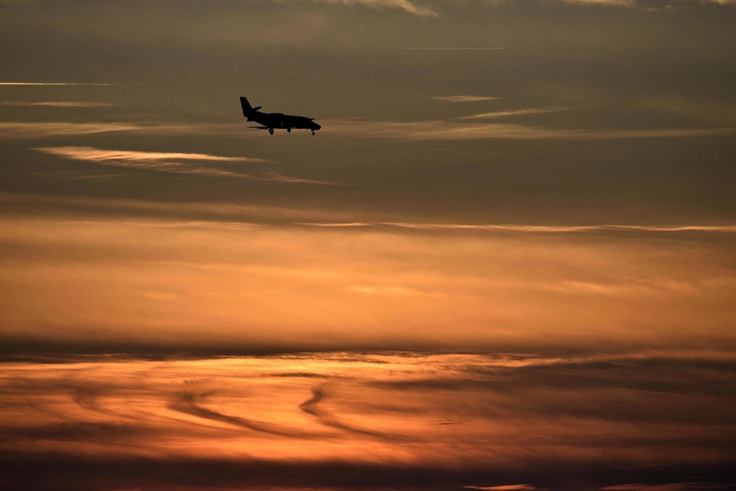 silhouet van een vliegtuig bij zonsondergang foto