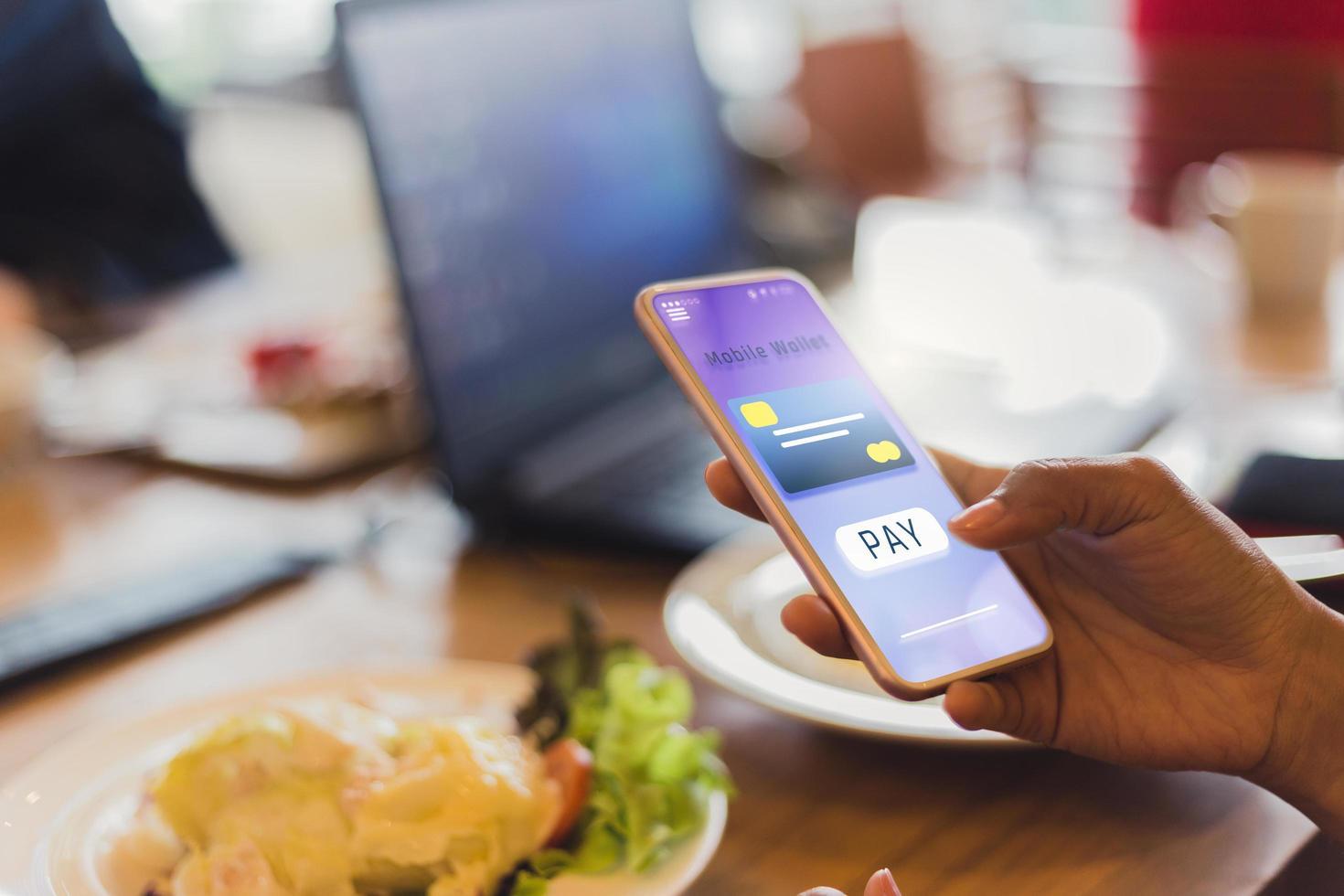 vrouw betaalt voor eten via mobiele telefoon foto