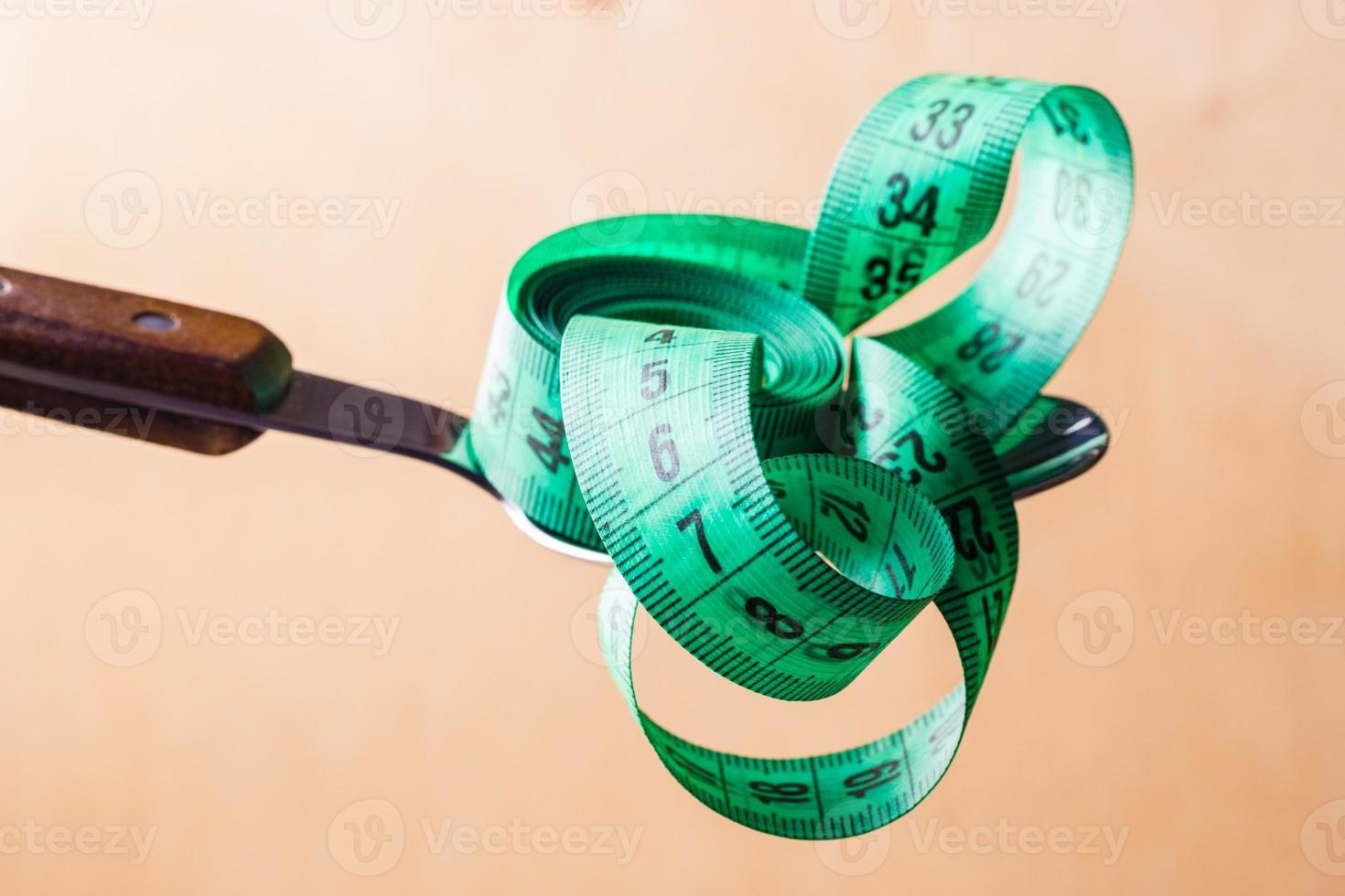 Cinta métrica verde en una cuchara de cocina foto