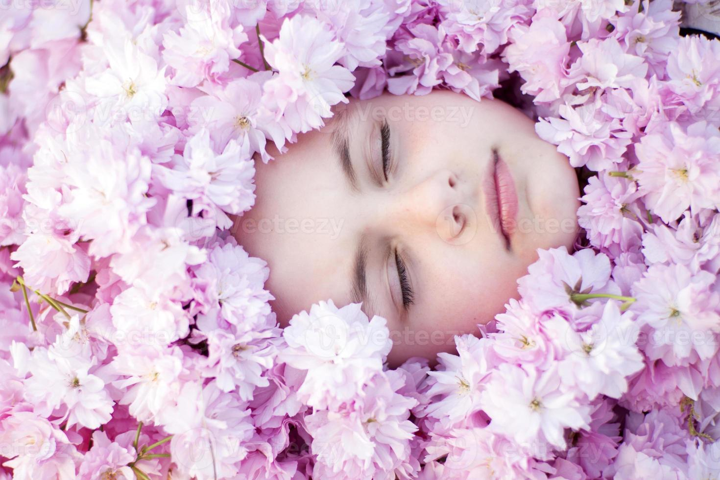 Face of small girl among flowers photo
