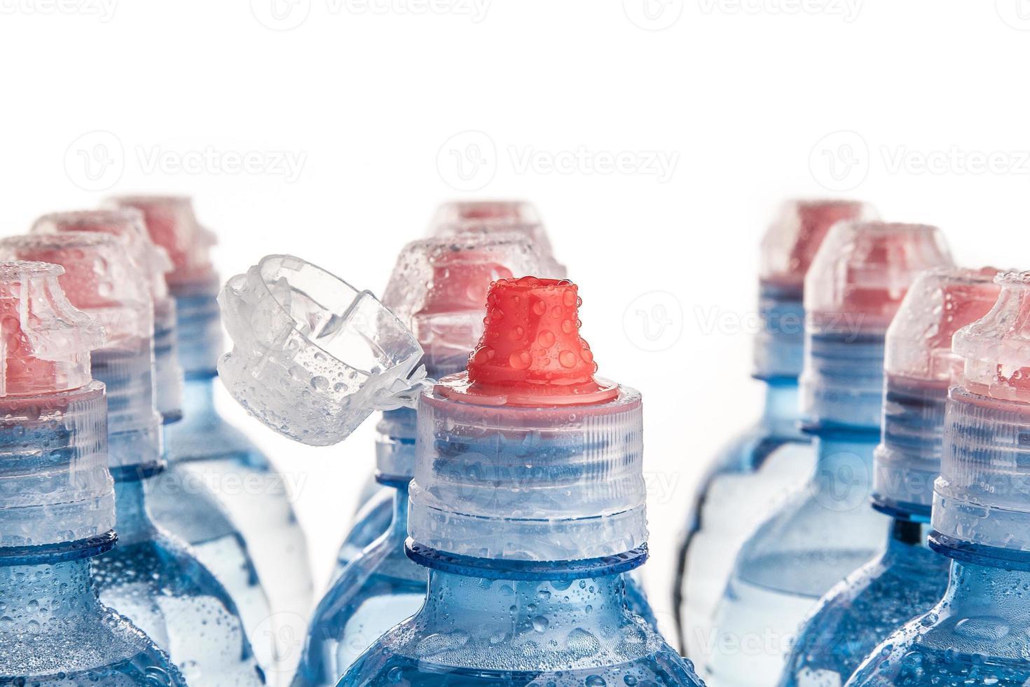 Botella de plástico de agua potable aislado en blanco foto