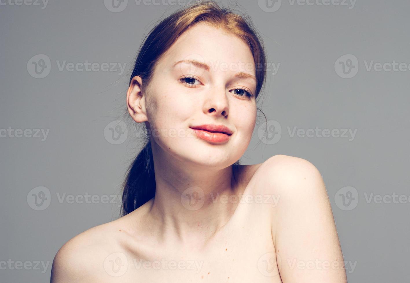 retrato de rosto de mulher bonita jovem em fundo cinza foto