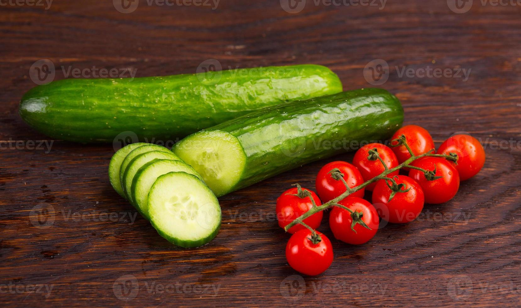 Cucumber amd tomatoes on wooden table photo