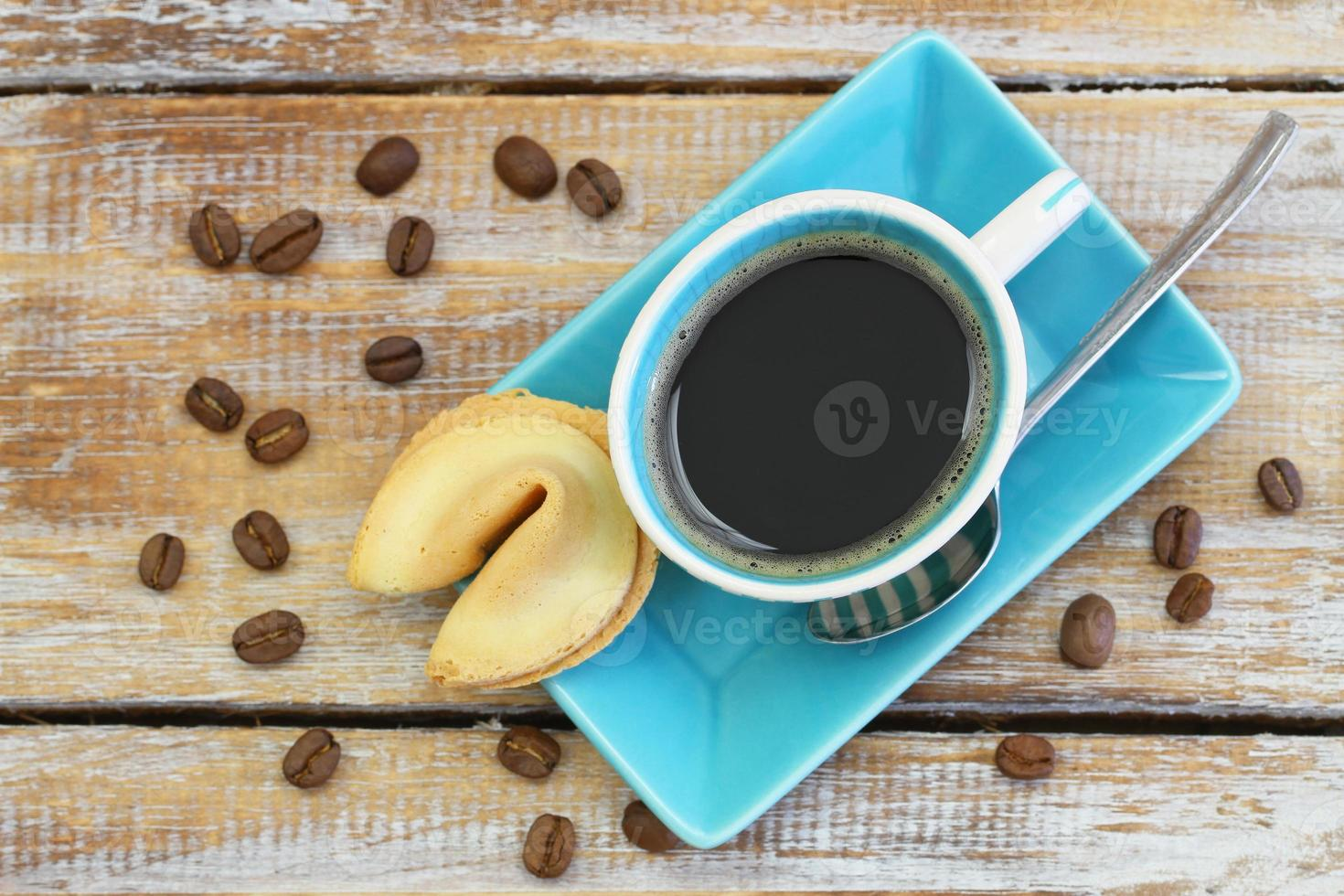 Coffee with fortune cookie on rustic wooden surface photo