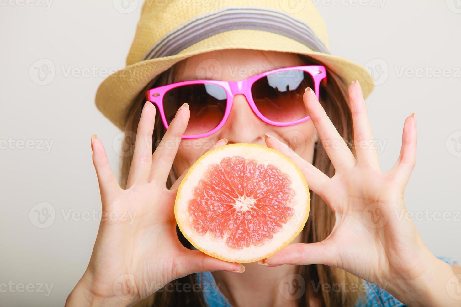 verão. turista garota segurando uma fruta cítrica de toranja foto