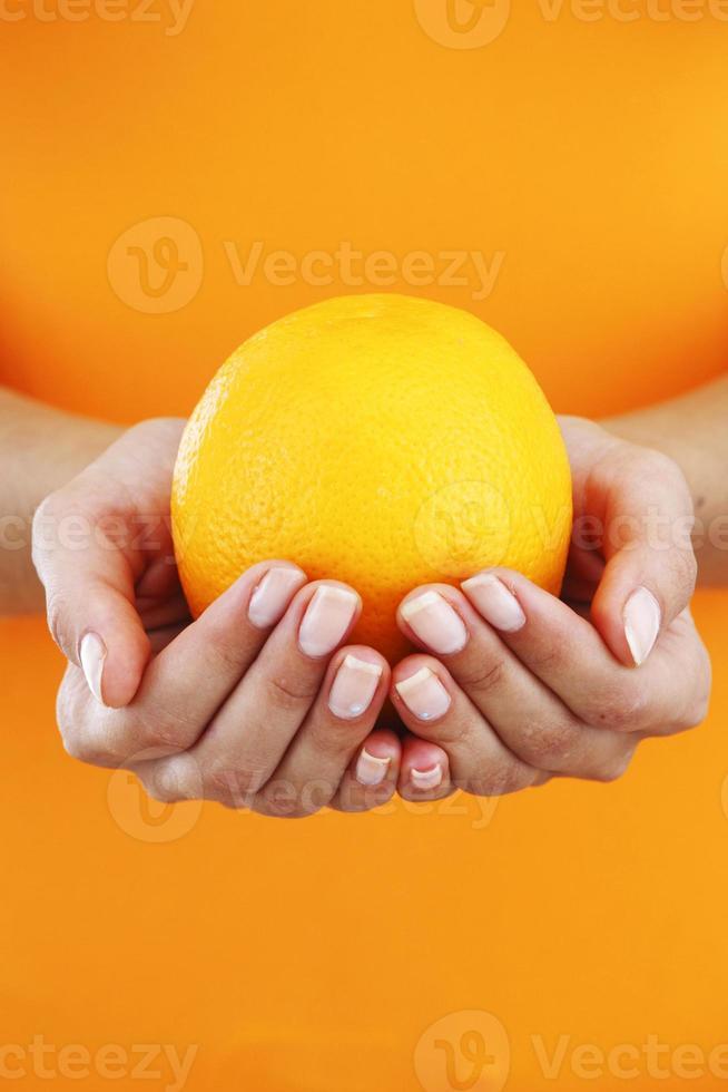sinaasappel in handen van de vrouw foto