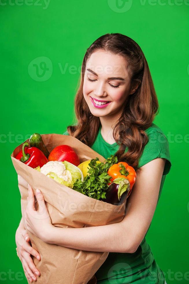 jeune femme avec un sac en papier de légumes. photo