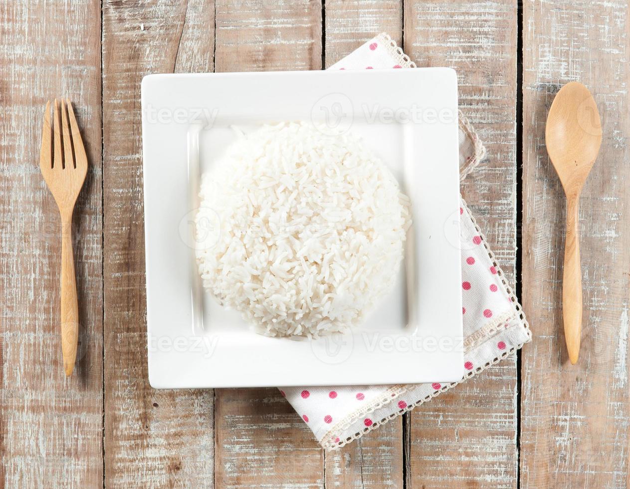 Cuenco lleno de arroz y cuchara sobre fondo blanco. foto