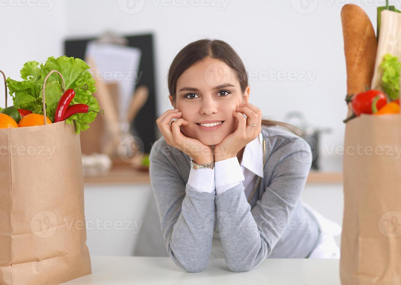 mujer joven con bolsa de compras de comestibles vegetales en foto
