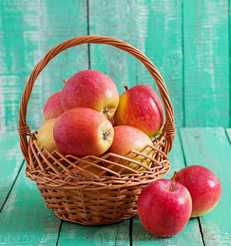 Manzanas rojas maduras en una canasta sobre fondo de madera foto