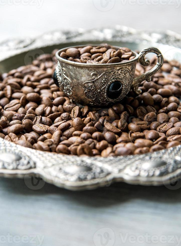 Granos de café en tazas de plata vintage sobre fondo de madera foto