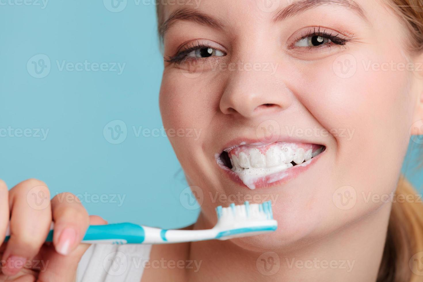 woman with toothbrush brushing cleaning teeth photo