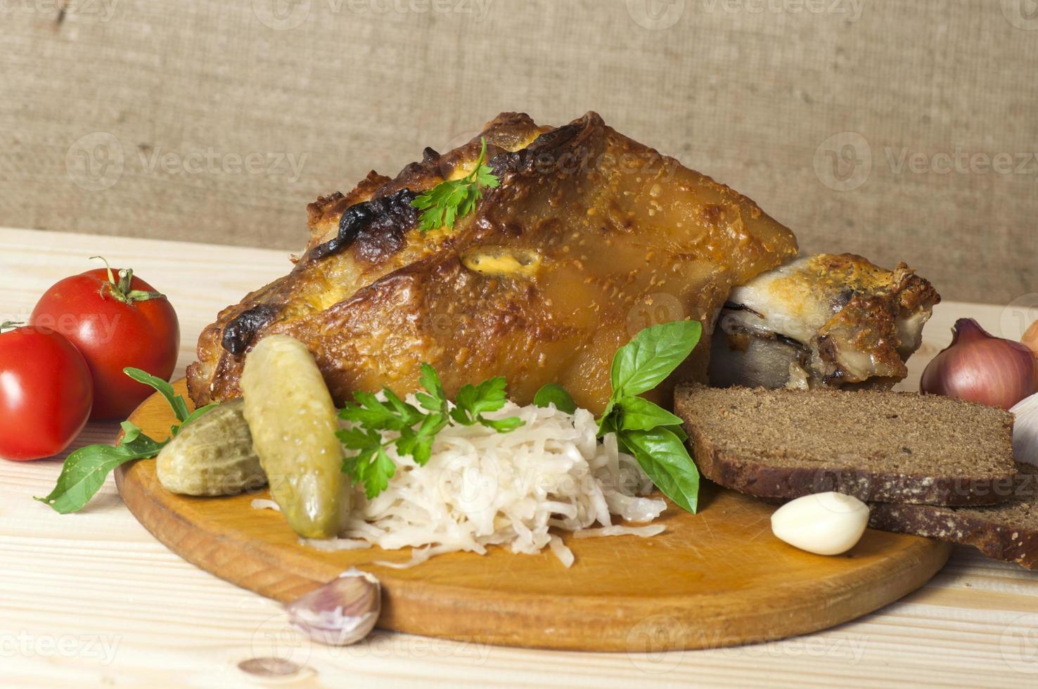pierna de cerdo asada servida con chucrut foto