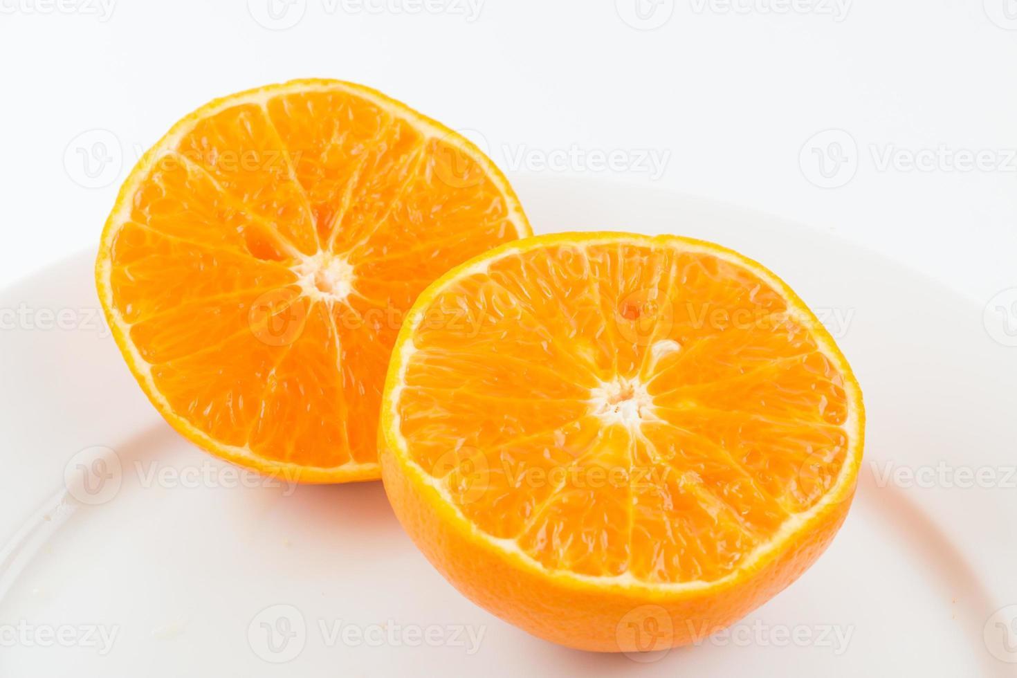 Media fruta naranja sobre fondo blanco, fresca y jugosa foto