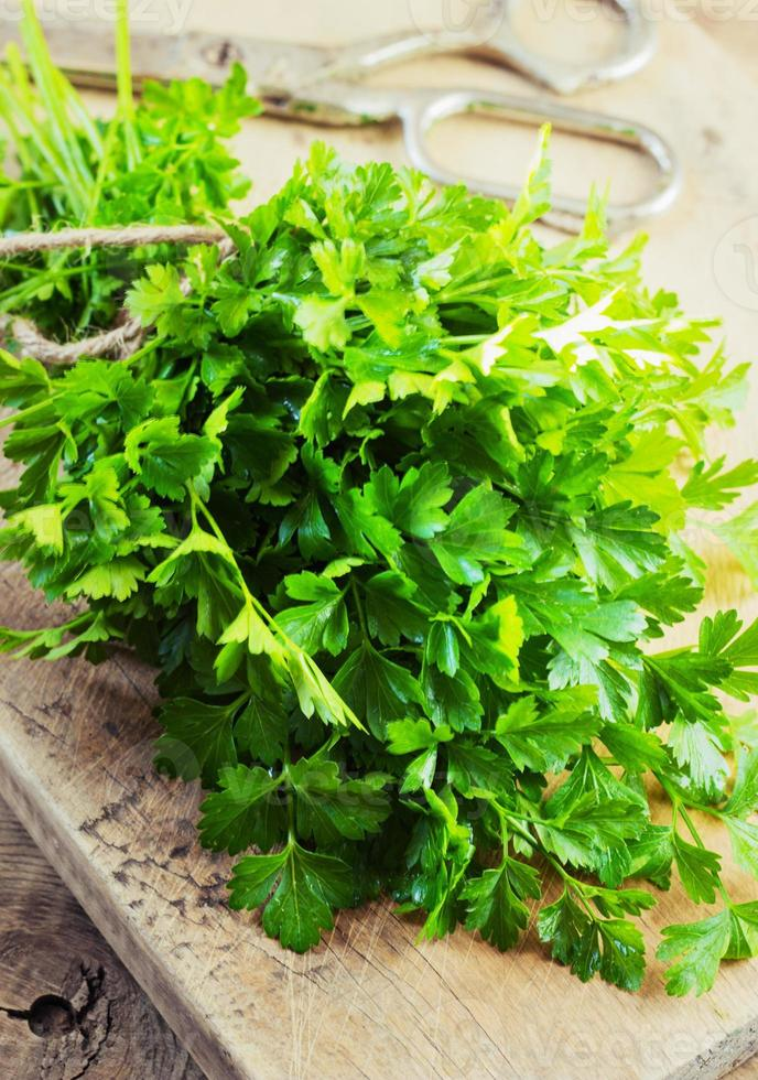Fresh green parsley on wooden background photo