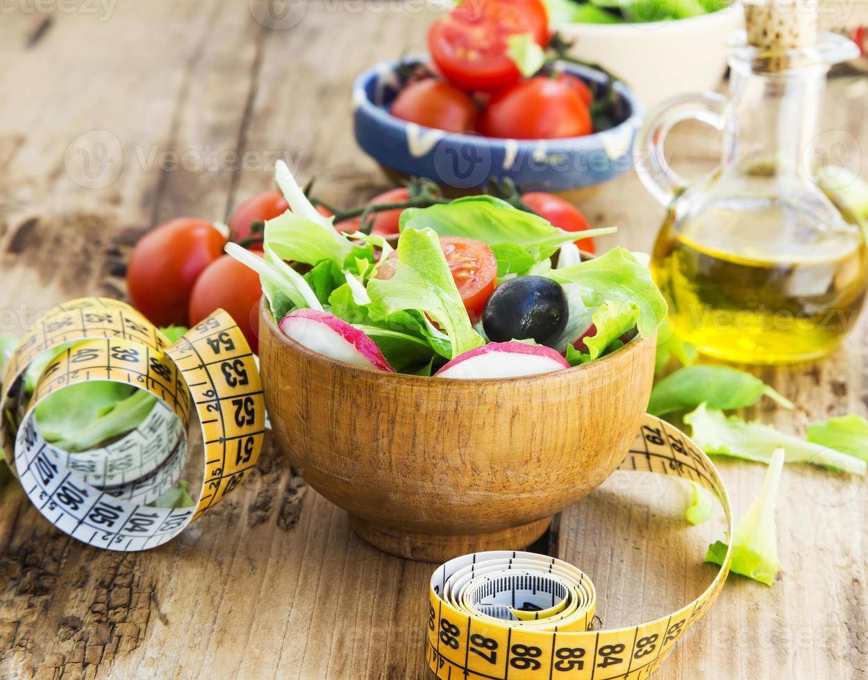 Ensalada de verduras saludables con cinta métrica concepto de dieta. foto
