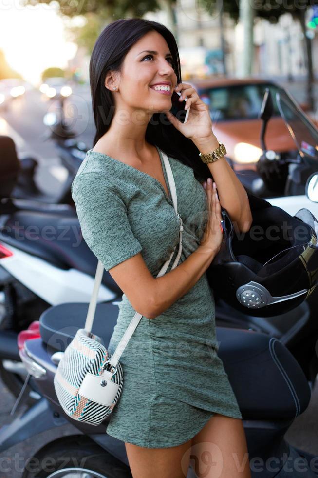 hermosa chica sentada en un scooter y hablando por teléfono. foto