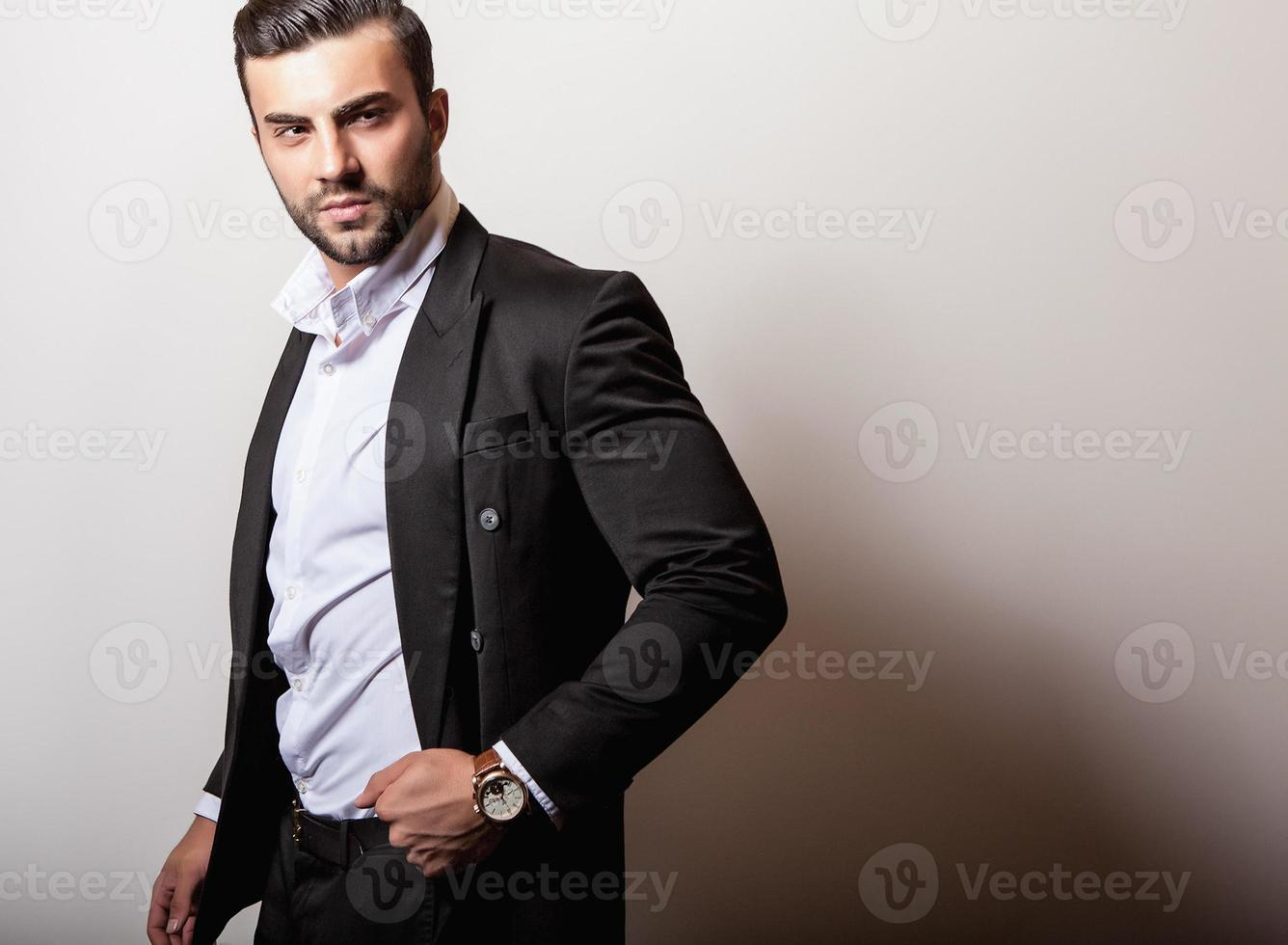elegante joven apuesto en traje clásico negro. foto